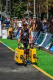 LVIV, UKRAINE - AUGUST 2017: A strong athlete a bodybuilder carries heavy iron suitcases, in exercise a farmer`s walk, on the stro Royalty Free Stock Photos