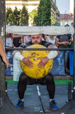 LVIV, UKRAINE - AUGUST 2017: A strong athlete a bodybuilder lifts a huge heavy stone yellow ball at Strongmen games Royalty Free Stock Photo