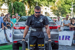 LVIV, UKRAINE - AUGUST 2017: Strong athlete the bodybuilder lifts the Toyota car in front of enthusiastic spectators at the Strong. Strong athlete the Stock Photography