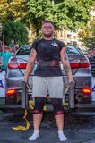LVIV, UKRAINE - AUGUST 2017: Strong athlete the bodybuilder lifts the Toyota car in front of enthusiastic spectators at the Strong. Strong athlete the Stock Photos
