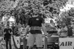 LVIV, UKRAINE - AUGUST 2017: Strong athlete the bodybuilder lifts the Toyota car in front of enthusiastic spectators at the Strong. Strong athlete the Royalty Free Stock Photos