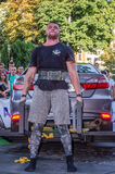 LVIV, UKRAINE - AUGUST 2017: Strong athlete the bodybuilder lifts the Toyota car in front of enthusiastic spectators at the Strong. Strong athlete the Stock Image