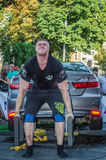 LVIV, UKRAINE - AUGUST 2017: Strong athlete the bodybuilder lifts the Toyota car in front of enthusiastic spectators at the Strong. Strong athlete the Royalty Free Stock Image