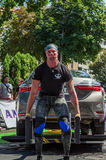 LVIV, UKRAINE - AUGUST 2017: Strong athlete the bodybuilder lifts the Toyota car in front of enthusiastic spectators at the Strong. Strong athlete the Royalty Free Stock Photo