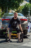 LVIV, UKRAINE - AUGUST 2017: Strong athlete the bodybuilder lifts the Toyota car in front of enthusiastic spectators at the Strong. Strong athlete the Stock Images
