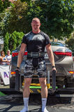 LVIV, UKRAINE - AUGUST 2017: Strong athlete the bodybuilder lifts the Toyota car in front of enthusiastic spectators at the Strong. Strong athlete the Royalty Free Stock Photography