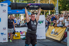 LVIV, UKRAINE - AUGUST 2017: A strong athlete picks up a huge heavy pack of barbell over his head in front of admiring spectators. A strong athlete picks up a Stock Images