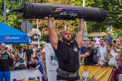 LVIV, UKRAINE - AUGUST 2017: A strong athlete picks up a huge heavy pack of barbell over his head in front of admiring spectators. A strong athlete picks up a Royalty Free Stock Photography