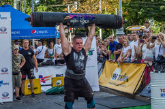 LVIV, UKRAINE - AUGUST 2017: A strong athlete picks up a huge heavy pack of barbell over his head in front of admiring spectators. A strong athlete picks up a Stock Photos