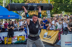 LVIV, UKRAINE - AUGUST 2017: A strong athlete picks up a huge heavy pack of barbell over his head in front of admiring spectators. A strong athlete picks up a Royalty Free Stock Photos