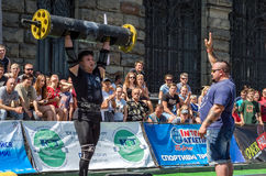 LVIV, UKRAINE - AUGUST 2017: A strong athlete picks up a huge heavy pack of barbell over his head in front of admiring spectators. A strong athlete picks up a Royalty Free Stock Image