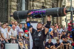 LVIV, UKRAINE - AUGUST 2017: A strong athlete picks up a huge heavy pack of barbell over his head in front of admiring spectators. A strong athlete picks up a Royalty Free Stock Images