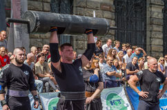 LVIV, UKRAINE - AUGUST 2017: A strong athlete picks up a huge heavy pack of barbell over his head in front of admiring spectators. A strong athlete picks up a Stock Photo