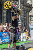 LVIV, UKRAINE - AUGUST 2017: A strong athlete picks up a huge heavy pack of barbell over his head in front of admiring spectators. A strong athlete picks up a Stock Photography