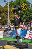 LVIV, UKRAINE - AUGUST 2017: A strong athlete picks up a huge heavy pack of barbell over his head in front of admiring spectators. A strong athlete picks up a Stock Image