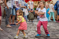 LVIV, UKRAINE - AUGUST 2016: Young children catching soap bubbles in the city, playing, joyful and radiating positive emotions, ha Stock Photography