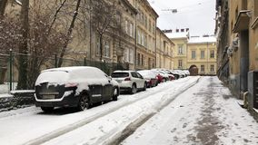 Lviv, Ukraine - December 24, 2018: Cars covered with snow are parked on the streets of old Lviv, Ukraine. Lviv, Ukraine - December 24, 2018: Cars covered with stock footage