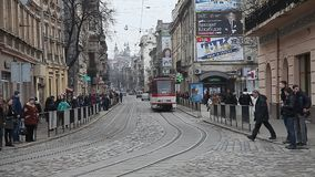 LVIV, UKRAINE - February 28, 2015 Busy street in center Lviv with tram riding. Passing cars and pedestrians crossing the street stock video