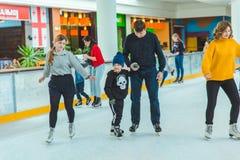 LVIV, UKRAINE - February 3, 2019: father teaching son how to skate on ski rink. Family time royalty free stock image