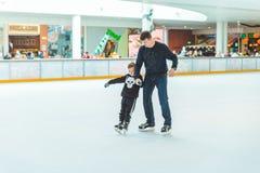 LVIV, UKRAINE - February 3, 2019: father teaching son how to skate on ski rink. Family time royalty free stock photos