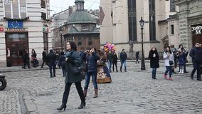 LVIV, UKRAINE - February 28, 2015 Lviv central square busy with pedestrians walking and seller of flowers and candy stock video