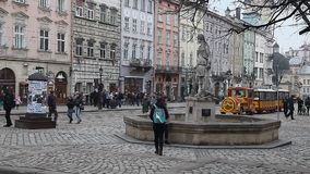 LVIV, UKRAINE - February 28, 2015 Lviv central square busy with pedestrians walking and tram riding stock footage