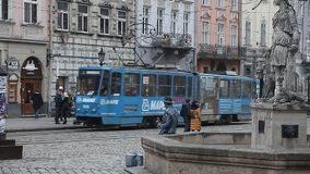 LVIV, UKRAINE - February 28, 2015 Lviv central square busy with pedestrians walking and tram riding stock video footage