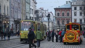 LVIV, UKRAINE - February 28, 2015 Lviv central square busy with pedestrians walking and tram riding. LVIV, UKRAINE - February 28, 2015 Lviv central square busy stock video footage