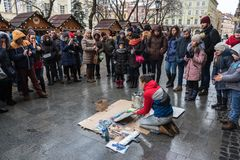 Lviv, Ukraine - January 21, 2018: Spray paint show for audience in the middle of the street, young beautiful sitting on the knees. Lviv, Ukraine - January 21 Stock Images