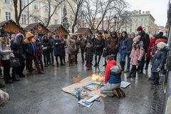 Lviv, Ukraine - January 21, 2018: Spray paint show for audience in the middle of the street, young beautiful sitting on the knees. Lviv, Ukraine - January 21 Stock Image