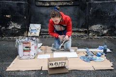 Lviv, Ukraine - 21 janvier 2018 : Exposition de peinture de jet pour l'assistance au milieu de la rue, jeune belle séance sur les Photographie stock libre de droits