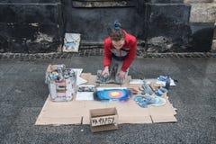 Lviv, Ukraine - 21 janvier 2018 : Exposition de peinture de jet pour l'assistance au milieu de la rue, jeune belle séance sur les Photographie stock