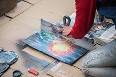 Lviv, Ukraine - 21 janvier 2018 : Exposition de peinture de jet pour l'assistance au milieu de la rue, jeune belle séance sur les Photos stock