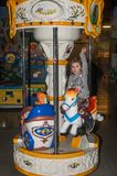 LVIV, UKRAINE - JANVIER 2018 : La petite fille avec du charme l'enfant va chercher un tour en parc d'attractions sur le carrousel Photographie stock