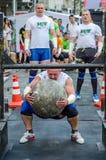 LVIV, UKRAINE - JUIN 2016 : L'homme fort fort de bodybuilder soulève une boule en pierre lourde énorme faite de marbre et la jett Photos stock