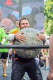 LVIV, UKRAINE - JUIN 2016 : L'homme fort fort de bodybuilder soulève une boule en pierre lourde énorme faite de marbre et la jett Photos libres de droits