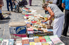 Lviv, Ukraine - July 2015: Men and women choose and buy, and sellers are selling old rare books and vintage items in the book mark Royalty Free Stock Image