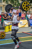 LVIV, UKRAINE - JULY 2016: Strong athlete bodybuilder pumped strongman with a heavy body raises the bar in front of a pack of enth Royalty Free Stock Image