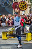 LVIV, UKRAINE - JULY 2016: Strong athlete bodybuilder pumped strongman with a heavy body raises the bar in front of a pack of enth Stock Photography