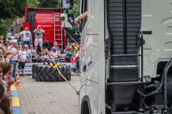 LVIV, UKRAINE - JULY 2016: Strong athlete strongman pulling a rope truck sitting with a partner is not huge tires Stock Image