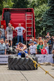 LVIV, UKRAINE - JULY 2016: Strong athlete strongman pulling a rope truck sitting with a partner is not huge tires Stock Photo