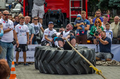 LVIV, UKRAINE - JULY 2016: Strong athlete strongman pulling a rope truck sitting with a partner is not huge tires Stock Images