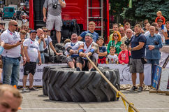 LVIV, UKRAINE - JULY 2016: Strong athlete strongman pulling a rope truck sitting with a partner is not huge tires Royalty Free Stock Photos