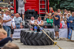 LVIV, UKRAINE - JULY 2016: Strong athlete strongman pulling a rope truck sitting with a partner is not huge tires Royalty Free Stock Photo