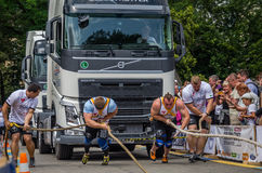 LVIV, UKRAINE - JULY 2016: Two strong athlete bodybuilder strongman pulling with ropes two huge truck in front of enthusiastic aud Royalty Free Stock Photography