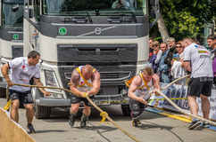 LVIV, UKRAINE - JULY 2016: Two strong athlete bodybuilder strongman pulling with ropes two huge truck in front of enthusiastic aud Royalty Free Stock Photos