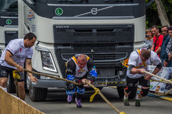 LVIV, UKRAINE - JULY 2016: Two strong athlete bodybuilder strongman pulling with ropes two huge truck in front of enthusiastic aud Stock Photo
