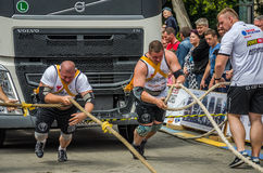 LVIV, UKRAINE - JULY 2016: Two strong athlete bodybuilder strongman pulling with ropes two huge truck in front of enthusiastic aud Royalty Free Stock Photo