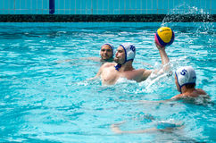 Lviv, Ukraine - July 2015: Ukrainian Cup water polo. Athlete team's water polo ball in a swimming pool and makes attacking shot on Royalty Free Stock Images