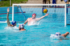 Lviv, Ukraine - July 2015: Ukrainian Cup water polo. Athlete team's water polo ball in a swimming pool and makes attacking shot on Royalty Free Stock Photography